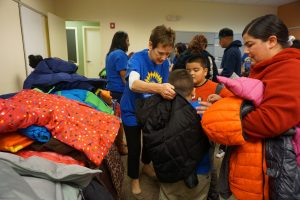 Photo of volunteers helping young children try on new coats during annual distribution event