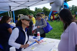 Photo of a volunteer sharing information about LCH with a pregnant woman at an outdoor community event