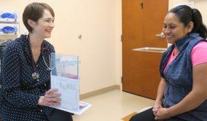 Foto de Kathryn Severson, APN, WHNP-BC, Enfermera Certificada de la Salud de la Mujer, enseña a una paciente sobre la salud reproductiva