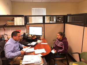 Photo of Eduardo, a Caseworker, in his office talking with a young woman about community resources