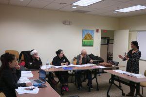 Foto de una maestra de GED enseñando una lección a un grupo de estudiantes en la Sala de Educación