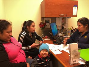 Photo of Maria, a Caseworker, talking with a family (a mother with her two young children) about health insurance enrollment options at a desk in an office