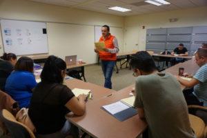 Foto de un instructor de ServSafe enseñando una clase sobre manipulación segura de alimentos a un grupo de estudiantes en la Sala de Educación