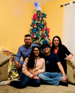 Photo of Cristina with her family in front of a Christmas Tree