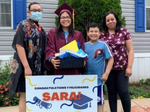 Escalera Graduate Smiles with LCH Staff and Family